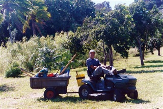 Dr. Marcel riding tractor on his organic garden plot in Hamakua, Hawaii